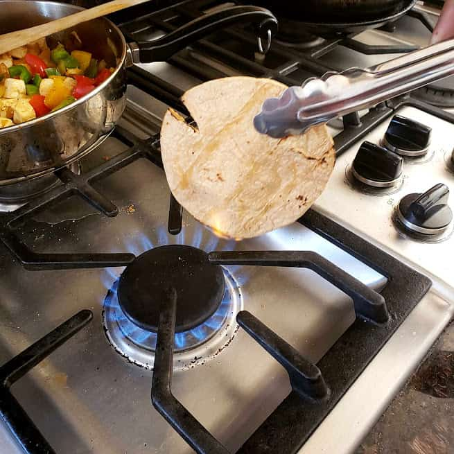 char grilling tortilla on a gas burner to make strret style paneer tacos.