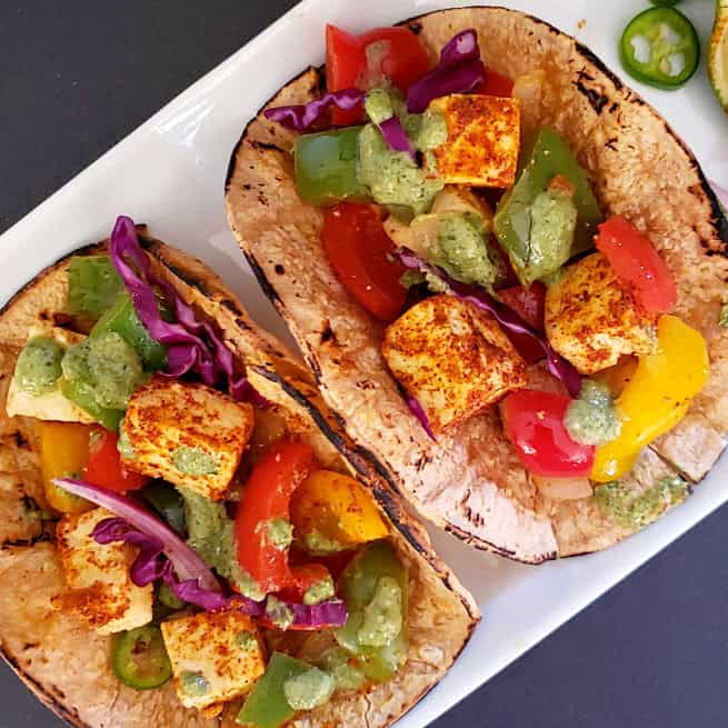 Paneer Fajita Tacos served with green sauce on white plate. This colorful recipe combines Indian Paneer with Mexican Taco seasoning making a lovely fusion.