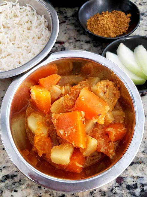 Pumpkin Potato curry with coconut and peanuts served with basamati rice in steel container.