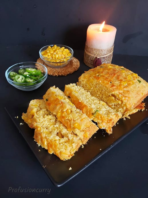 Southern style cornbread sliced and served in beautiful setting with candle lit in the background.
