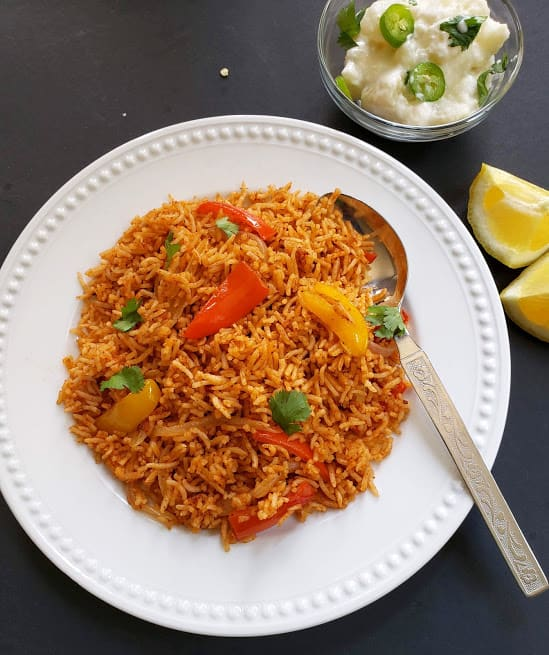 Tawa Pulao served on white plate with spoon