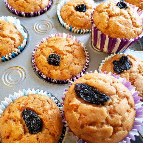 Freshly baked Pumpkin Spice Muffins decorated with raisins on top ready to be served. A profusioncurry recipe that is vegan and gluten free.