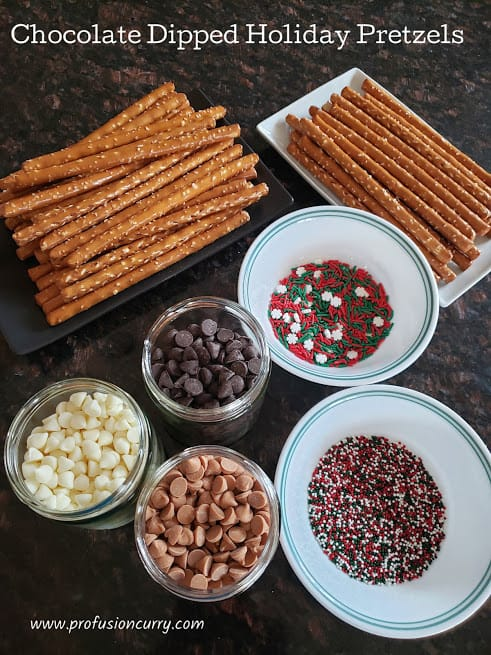 Chocolate dipped holiday pretzels ingredients display.