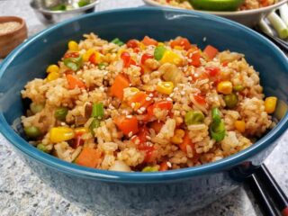 Instant Pot Vegetable Fried rice served in a blue bowl along with sesame seeds and green onions. This fried rice recipe akes best easy meal in one pot.