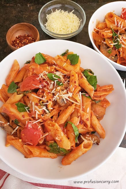 Delicious pasta in tomato cream sauce served in white dinner plate with parmesan cheese and red pepper flakes garnish. This instantpot pasta is ideal 20 minute weeknight dinner recipe.