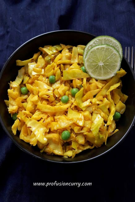 Turmeric Cabbage and peas stir-fry served in a bowl with two lime wedges for garnish.