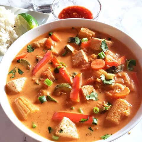 Thai Red curry with vegetables and tofu close up shot showing heaps of vegetables and tofu in a white bowl and garnished with green onions and cilantro. This profusioncurry recipe is vegan and gluten free.