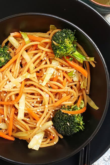 Close up image of Instantpot Lo Mein Noodles showing soft and moist texture. These noodles are cooked with colorful veggies and are garnished with sesame seeds.