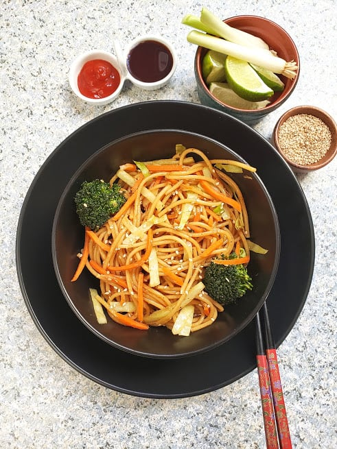 Vegetable lo mein noodles served in black bowl and chopsticks on the side.