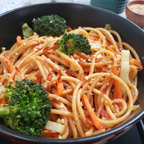 Chinese lo mein noodles served with colorful veggies and sesame garnish in a black container. This profusioncurry recipe can be made in Instantpot or stove top.