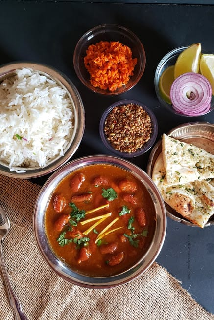 Indian dinner with Rajma masala curry, white rice, garlic naan, carrot pickle, flaxseed chutney and cut onions served in ethnic looking copper containers.