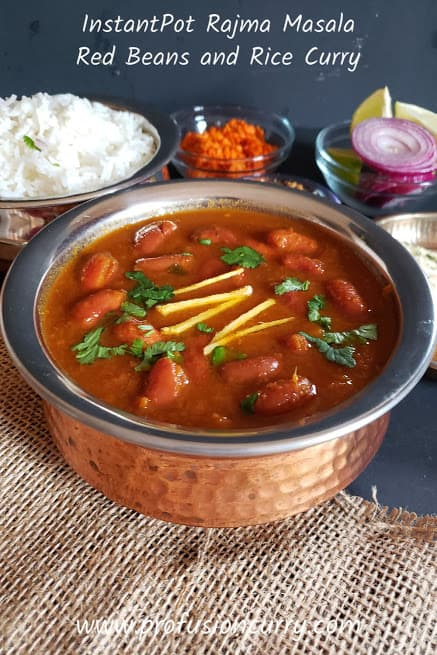 Ethnic copper serving container full of Rajma curry garnished with juliened ginger and chopped cilatro leaves. White basmati rice , red onion and lemon wedges in the background for complete dinner serving.