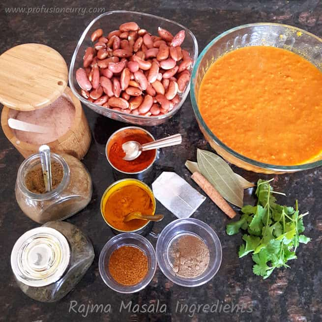 all the ingredients needed to make Rajma Curry gathered around on black granite countertop.
