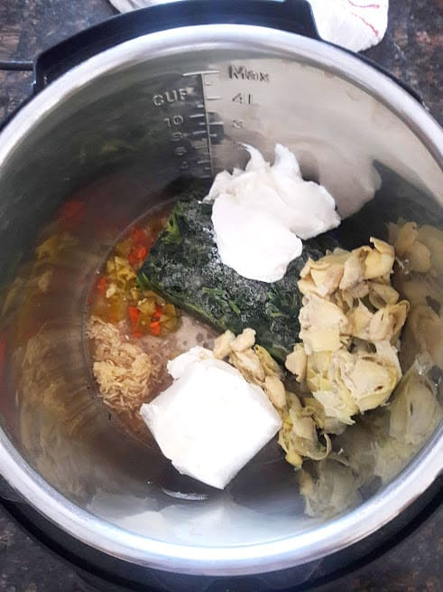 Process shot showing all the ingredients dumpled into Instantpot to make SPinach Artichoke dip