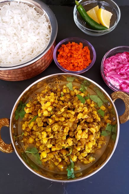 Indian Sprouts Curry served in copper container alog with steamed wihte rice, beetroot raita, carrot pickle and lemon wedges and cut onions. This wholesome meal is classic curry recipe by Profusioncurry.