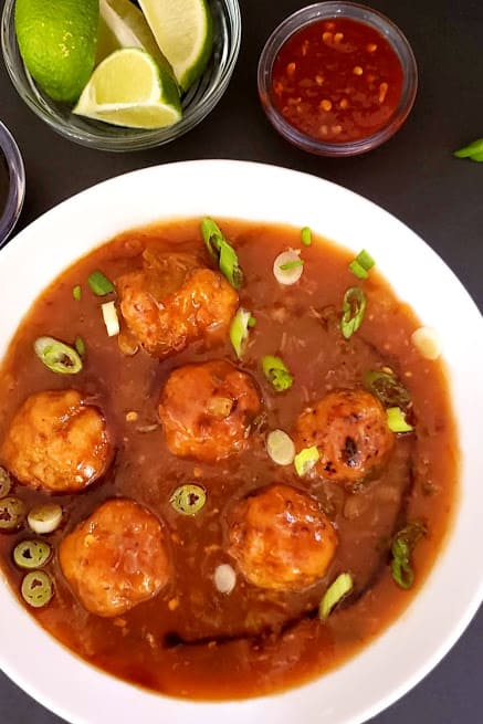 Delicious vegetable manchurian served in white bowl with green onion garnish. This delicious Profusioncurry recipe is popular Indo Chinese street food.