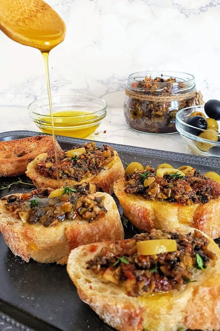 a wooden spoon drizzing olive oil over olive tapenade topped toasts.