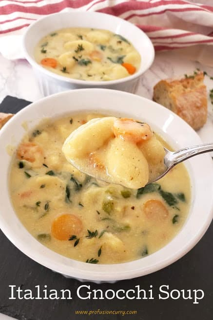 A spoonful of creamy soup and gnocchi showing creamy and hearty texture of delicious soup recipe.