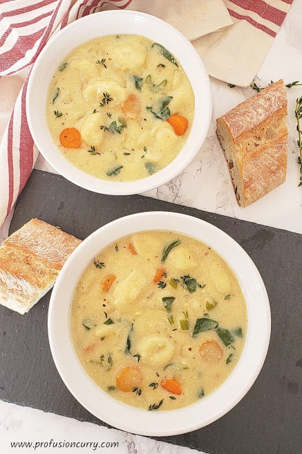 Two white soup bowls with Italian Creamy Gnocchi and Vegetable Soup served along with crusty bread