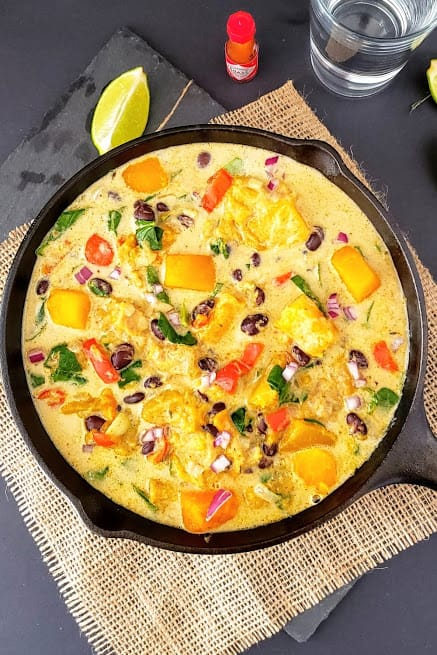 Colorful creamy butternut squash, black beans, bells peppers and spinach cooked in creamy stew served in cast iron skillet.