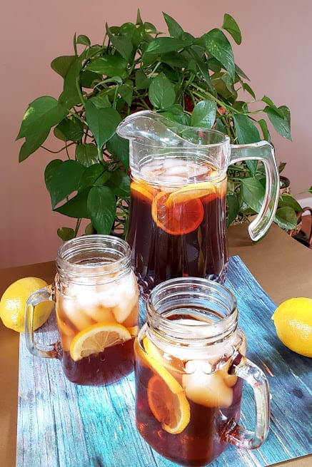 Serving the ice cold tea in a glass pitcher and two glass mason jars. There are bright yellow lemons around.
