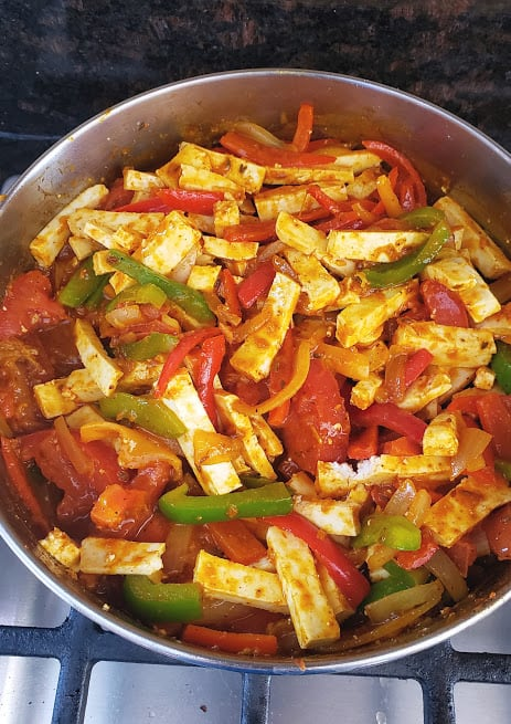 A close up shot of stir fry pan full of colorful veggies and paneer stripes coated in tomato gravy.