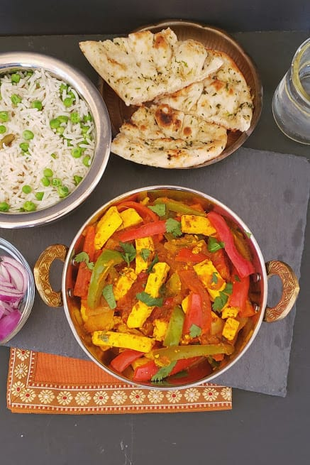 An overhead shot of Indian Dinner including Paneer Jalfrezi in kadhai, basmati rice with peas, naan and cut up onions and lemon.