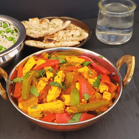 Stir fried paneer and colorful veggies in tangy Indian masala sauce sered in copper container along with peas pulao, naan and salad.