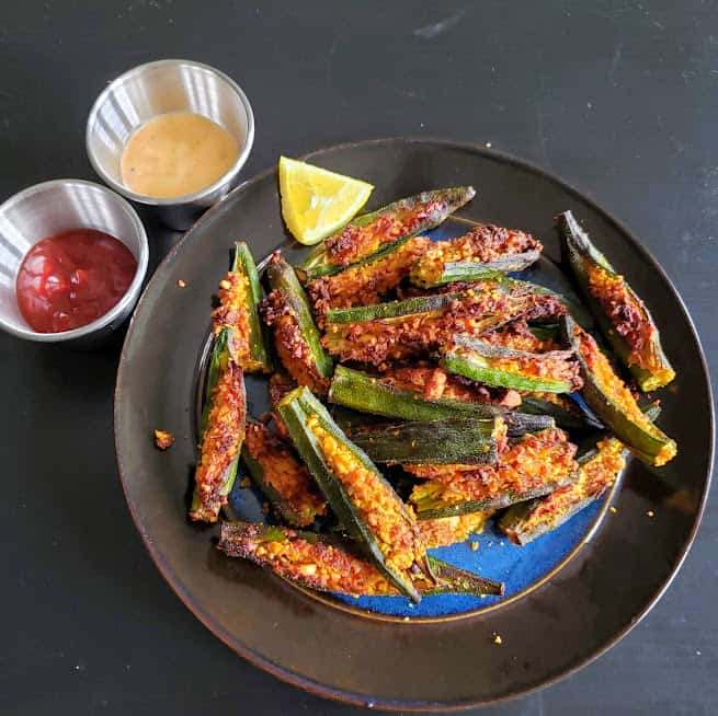 Crispy okra stuffed with ndian spices served on black dinner plate.