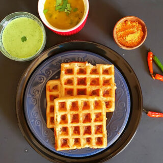 Stack of dosa waffles served with vegetable sambar, cilantro chutney and dry chutney. This savory waffle recipe is glutenfree and vegan.