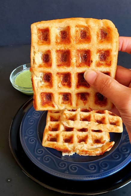 A hand holding golden brown crispy dosa waffle. This indo-american fusion recipe os kid friendly, low calorie and delicious.