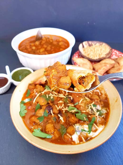A spoon full of chole, samosa bites and chutneys scooped from the chat serving plate.