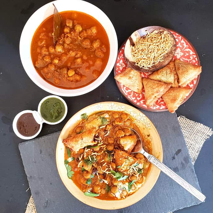 An overhead shot of food serving chickpea curry, baked samosa, two different chuntneys and a prepared plate of layered chat.