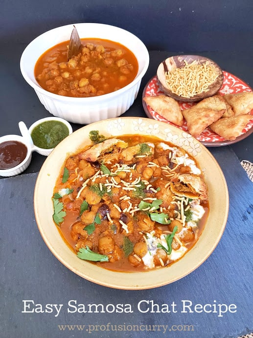 A full of serving of Indian style chat. It includes assembled plate of samosa chat along with chole curry and sev and chutney.