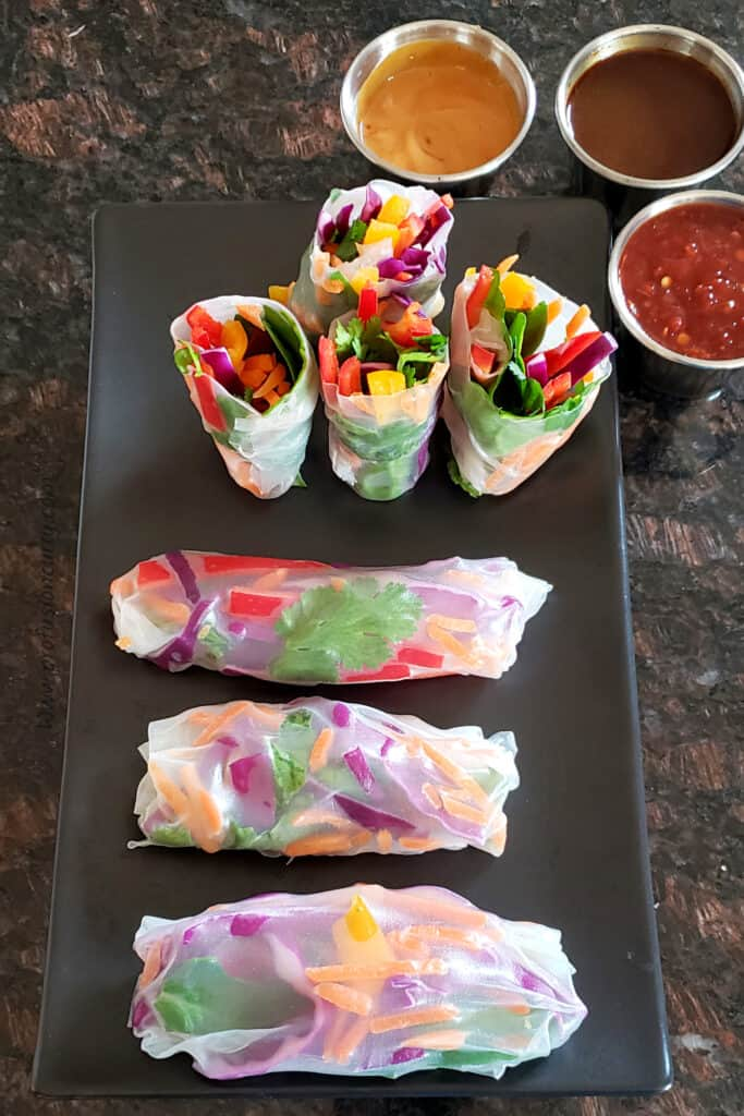 A lunch serving of fresh summer rolls along with three dipping sauces.
