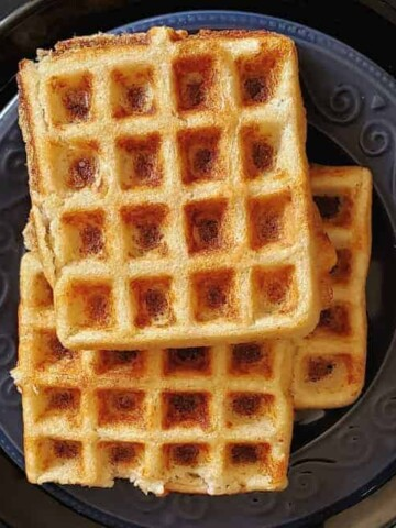 Savory Multigrain dosa waffles served on blue and black dinner plate.
