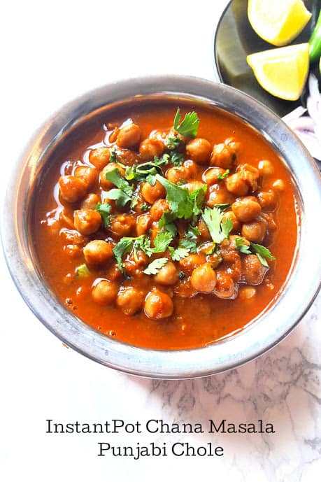 A serving platter full of chickpeas soaked in masala curry and garnished with cilantro leaves.