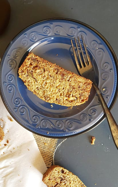 A slice of vegan banana bread served on blue plate with a fork on the side.