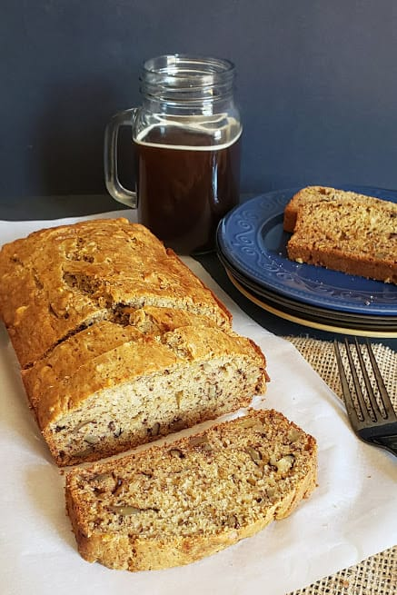 A sliced loaf of vegan banana bread on parchement paper with black coffee mason jar in the background.