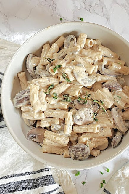 Creamy sauce coated pasta and mushrooms served in white stone bowl with thyme and red chili flakes.