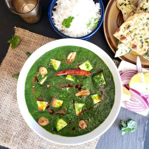 A white bowl full of spinach and paneer curry garnished with oil and garlic tempering. The white steamed rice and garlic naan in the background.