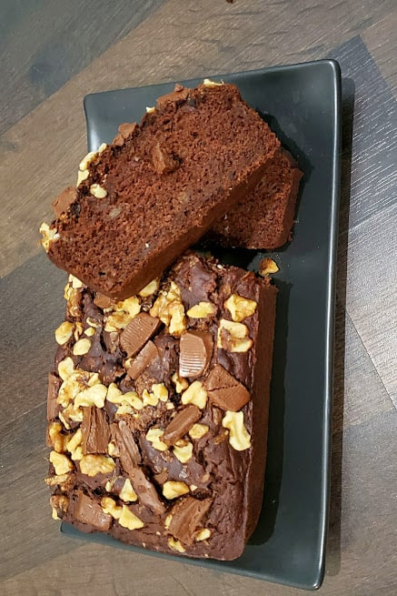 2 slices of chocolate banana bread along with rest of the bread served on the black serving platter.