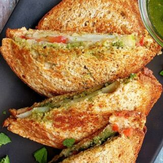 Two masala toast sandwiches cut into half and served on black serving plate.