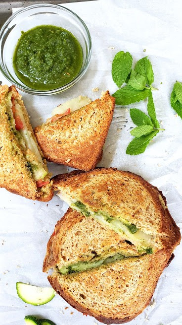 Green chutney laced bread toast sandwiches arranged on white parchement paper with mint leaves on the side.