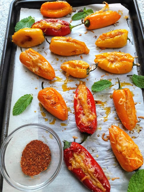 Cheese and potato stuffed peppers arranged on parchment paper and baking tray.
