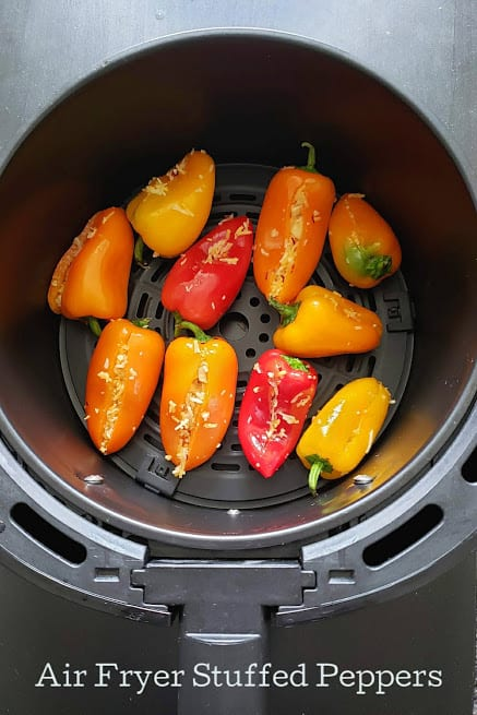 Colorful sweet peppers are stuffed with filling and arranged on air fryer tray.