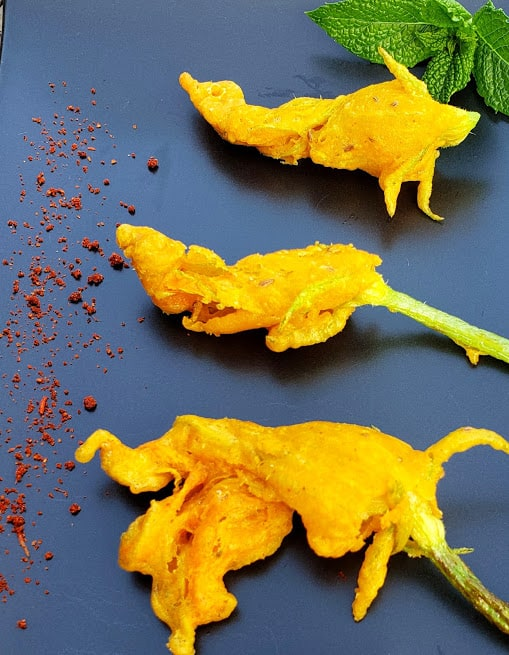 Indian style zucchini blossom fritters served on black serving platter with dry chutney