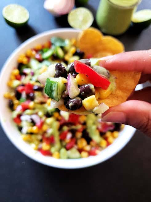 A hand holding tortilla chip and black bean salad . This colorful salad can also be served as a dip.
