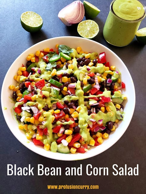 A serving platter full of black bean and corn salad drizzled with lime green dressing.