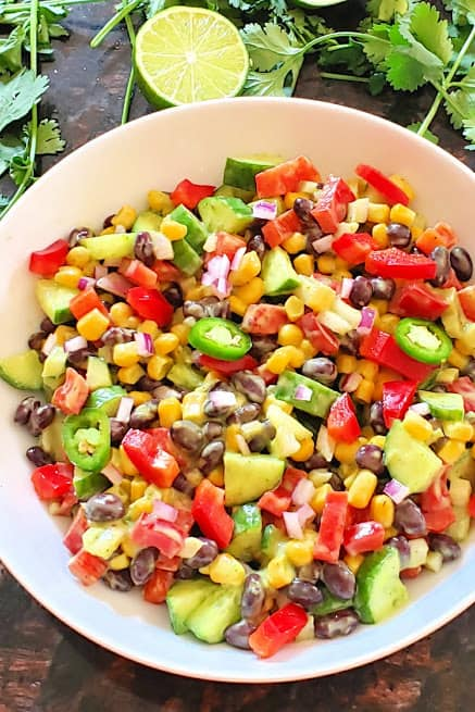 Black bean and corn salad along with avocado cilantro lime dressing served in a white salad bowl. This wholesome salad is perfect for summer lunches.